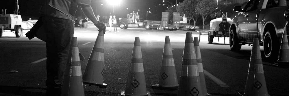 A worker lays traffic ones on Lincoln Boulevard outside Los Angeles International Airport, as roads are closed to move space shuttle Endeavour